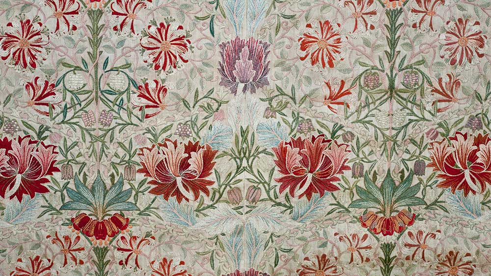 En detalj från ett broderi med mönstret Honeysuckle från 1876 av Morris & Co. Bilden kommer från William Morris Gallery i London, Borough of Waltham Forest.